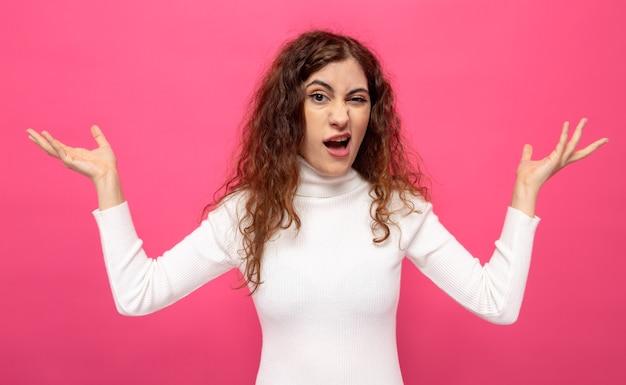 Молодая красивая женщина в белой водолазке со скептическим выражением лица с поднятыми руками, стоя над розовой стеной