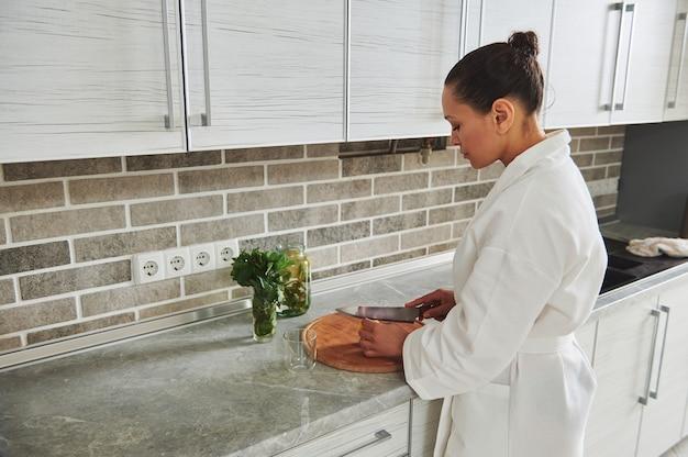 レモンミント水を準備するために木の板にレモンを切る白いワッフルバスローブの若い美しい女性。朝のルーチン、健康的な食事の概念