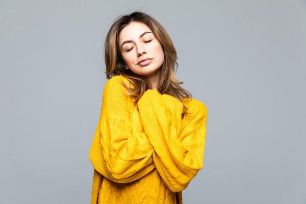 Молодая красивая женщина в желтый повседневный свитер, стоя со скрещенными руками, изолированные на серую стену