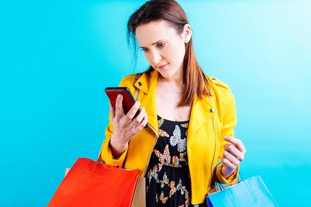 Молодая красивая женщина в желтой куртке на синем фоне, задумчиво глядя на смартфон с хозяйственными сумками. концепция шопоголической жертвы моды