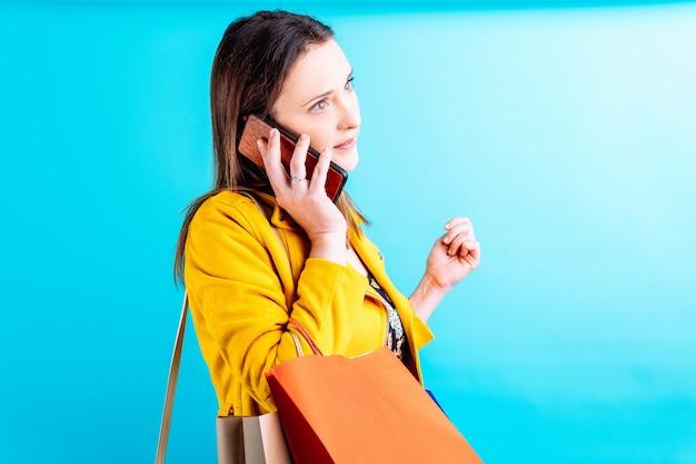 Молодая красивая женщина в желтой куртке на синем фоне, задумчиво говоря на смартфоне с хозяйственными сумками. концепция шопоголической жертвы моды