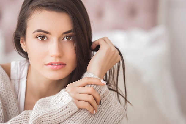 Young beautiful woman indoors. portrait of attractive woman in knitted clothes.