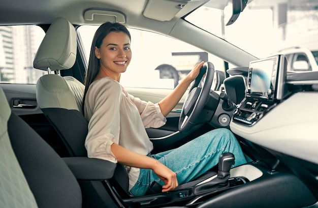 若い美しい女性が自動車販売店で新しい車を選んでいます。カーサロンの女性。車を買う女性。