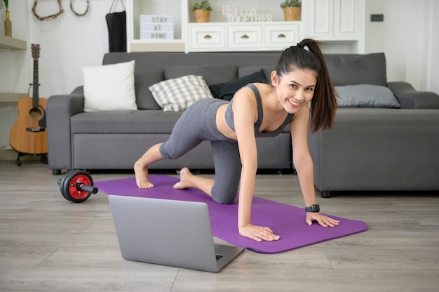 A young beautiful woman is doing the mountain climber exercise at home