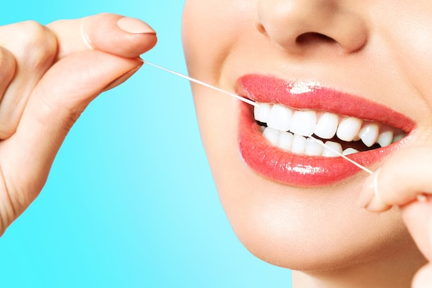 Young beautiful woman is engaged in cleaning teeth. beautiful smile healthy white teeth. a girl holds a dental floss. the concept of oral hygiene.