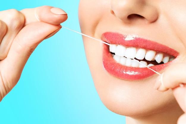 若い美しい女性は歯のクリーニングに従事しています。美しい笑顔の健康的な白い歯。女の子がデンタルフロスを持っています。口腔衛生の概念。