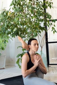 Молодая красивая женщина занимается растяжкой в комнате с растениями.