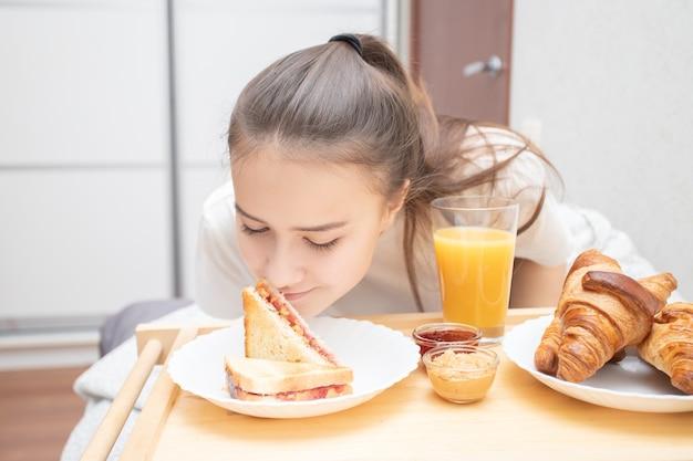 若い美しい女性はベッドで朝食を楽しんでいます。クロワッサン、オレンジジュース、ピーナッツバターとラズベリージャムサンドイッチ。