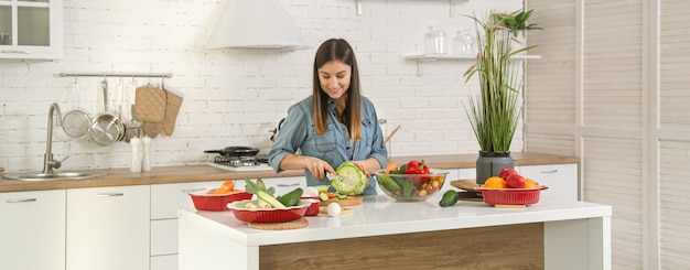 A young beautiful woman is preparing a salad of various vegetables in the kitchen. the concept of a healthy diet and lifestyle.