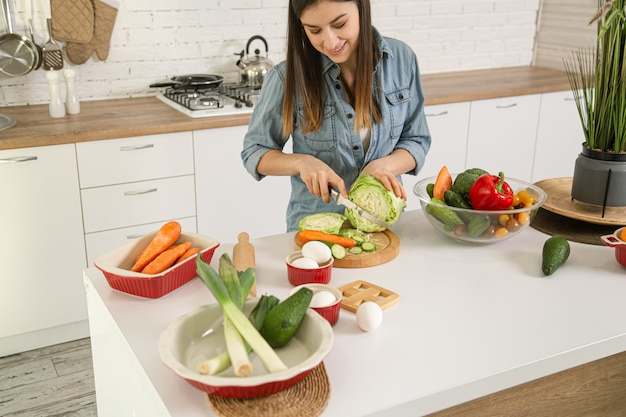 A young beautiful woman is preparing a salad of various vegetables in the kitchen.