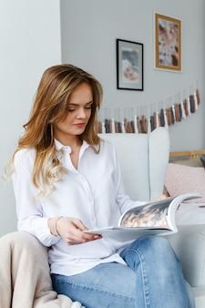 若い美しい女性は、居心地の良い明るいリビングルームの椅子に座って、雑誌を読んでいます