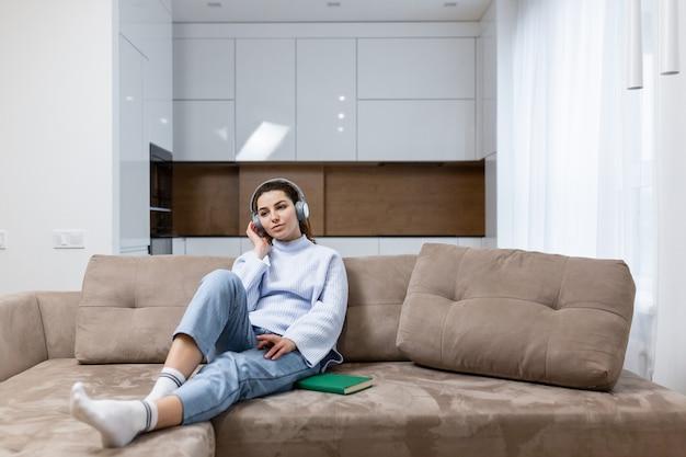 Молодая красивая женщина отдыхает дома, сидит на диване и слушает музыку в наушниках