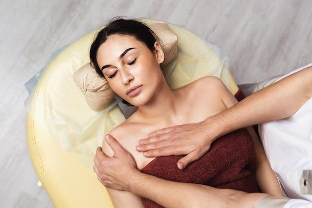 若くてきれいな女性は、スパ サロンで鎖骨の領域でマッサージの手順中に休んでいます。