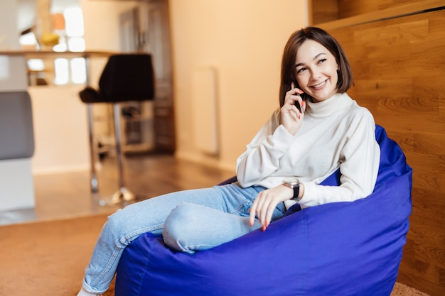 Young beautiful woman is sitting in bright violet bag chair using her phone texting