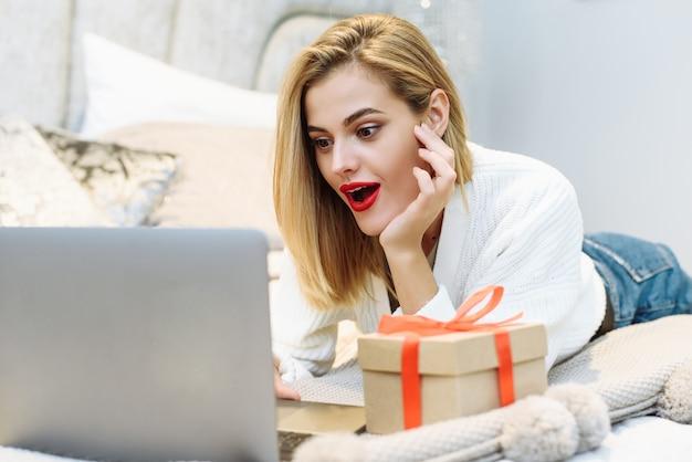 젊은 미인은 인터넷 사이트의 할인에 놀라고 크리스마스를 준비합니다.
