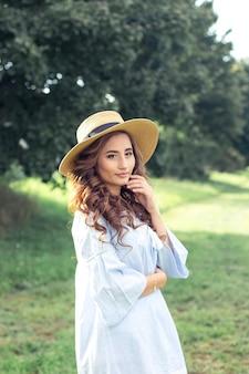 아름 다운 젊은 여자는 공원에서 걷고있다. 여름. 한 소녀가 봄에 걷고 있습니다. 들. 따뜻한.