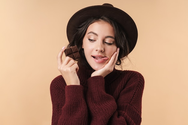 Young beautiful woman isolated over beige wall wall holding chocolate licking lips.
