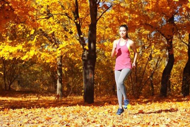 秋の公園でジョギング若い美しい女性
