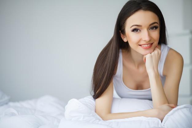 집에서 침대에 점프 젊은 아름 다운 여자