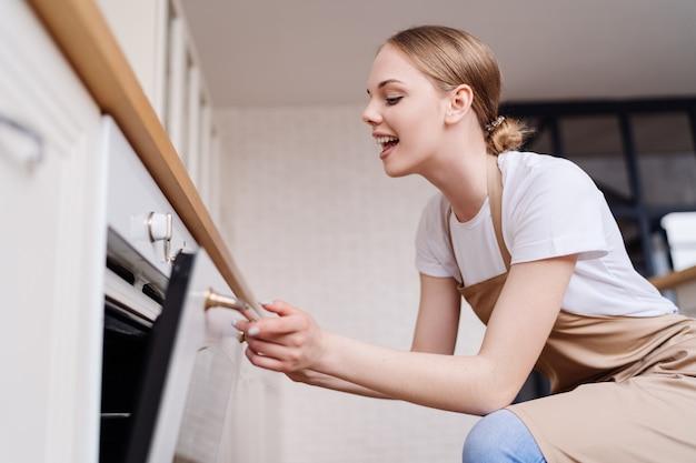 Giovane bella donna in cucina in un grembiule da forno