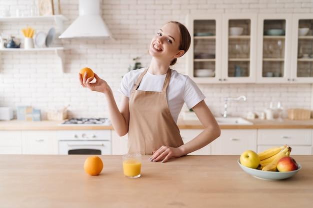 Giovane bella donna in cucina con grembiule, frutta e succo d'arancia orange