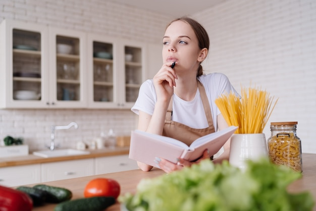 Young beautiful woman in the kitchen in an apron writes down her favorite recipes next to fresh vegetables