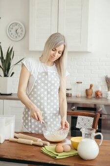 若い美しい女性は、キッチンでクッキーを焼くために生地をこねます。調色。