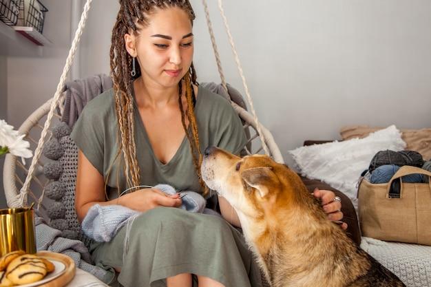 家でぶら下がっているマクラメスイングで編み物をする若い美しい女性。灰色の背景。