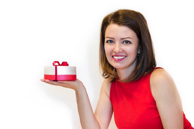 Young beautiful woman, lady, in red holiday clothes with snowy smile holding a gift box.