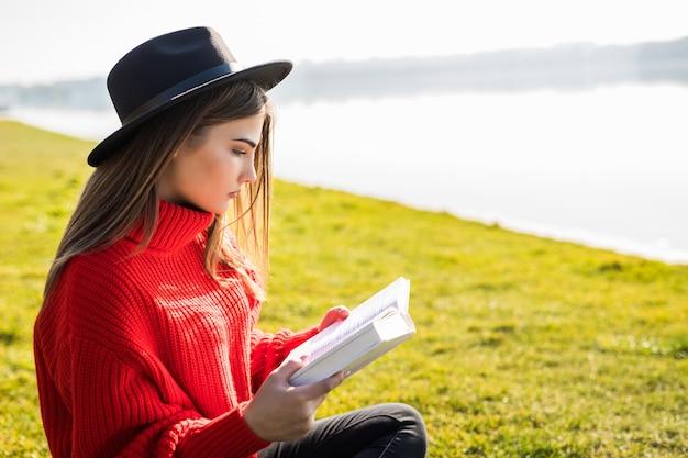 Молодая красивая женщина лежит на зеленом поле и читает книгу.
