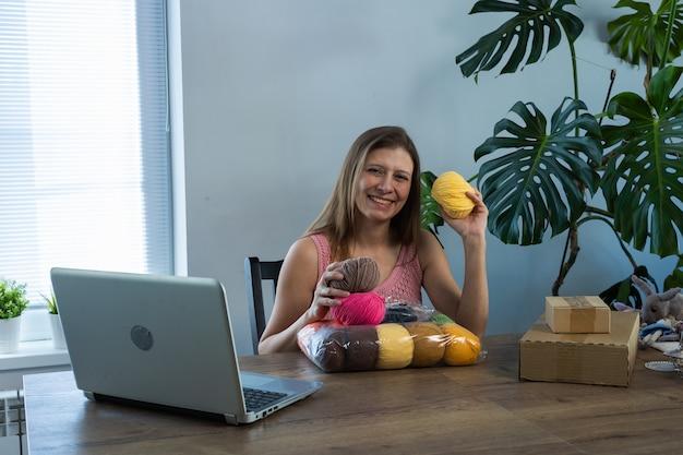 젊고 아름다운 여성이 집에서 비디오 블로그를 이끌고 새로 받은 상품 포장 풀기에 대한 내용을 씁니다.