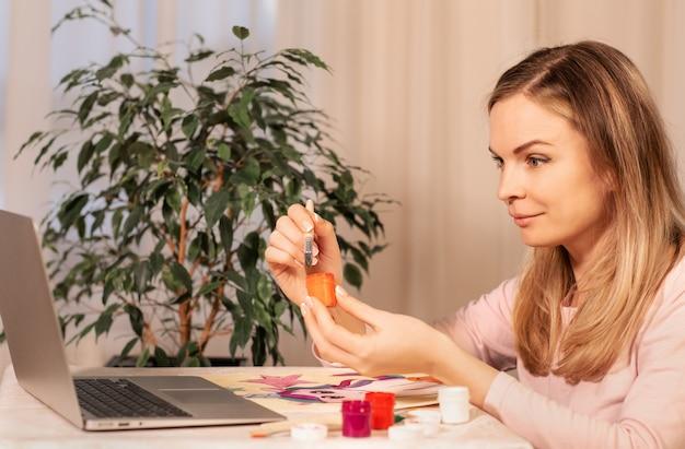 ノートパソコンのインターネットでアートレッスンをオンラインで学ぶ若い美しい女性。