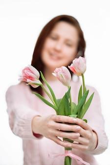 젊은 아름다운 여성 가벼운 스웨터는 흰색 바탕에 분홍색 튤립을 제공합니다. 흐림 초상화, 선택적 초점.