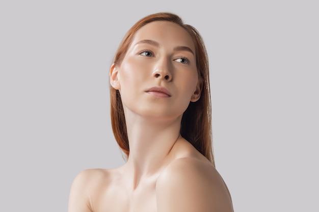 Giovane bella donna in biancheria che posa isolata sopra bellezza naturale della parete grigia dello studio