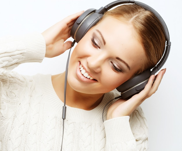 Young beautiful woman listening the music from headphones