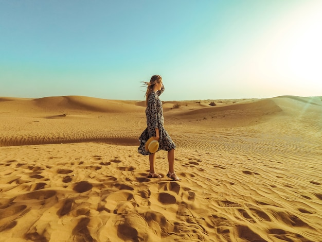 Young beautiful woman in long dress and with a hat in the middle of the dubai desert with sunlight