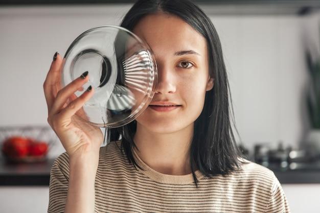 カメラを見て、顔の近くに空のガラス受け皿を保持している若い美しい女性