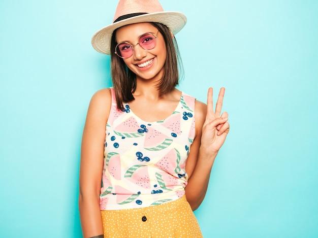 帽子でカメラを見て若い美しい女性。カジュアルな夏の白いtシャツと丸いサングラスの黄色いスカートのトレンディな女の子。肯定的な女性は顔の感情を示しています。ピースサインを表示します