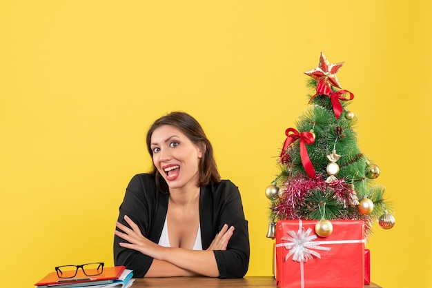 자랑스럽게 뭔가를보고 노란색 사무실에서 장식 된 크리스마스 트리 근처 테이블에 앉아 젊은 아름 다운 여자