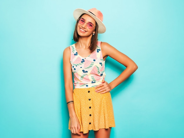 Young beautiful woman looking at camera in hat. trendy girl in casual summer white t-shirt and yellow skirt in round sunglasses. positive female shows facial emotions. funny model isolated on blue