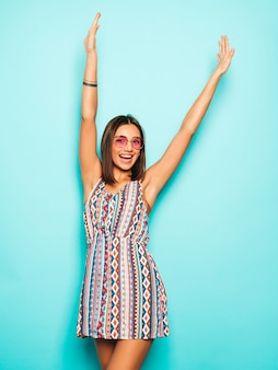 Young beautiful woman looking at camera. trendy girl in casual summer dress and round sunglasses. positive female shows facial emotions. model raising her hands and celebrating