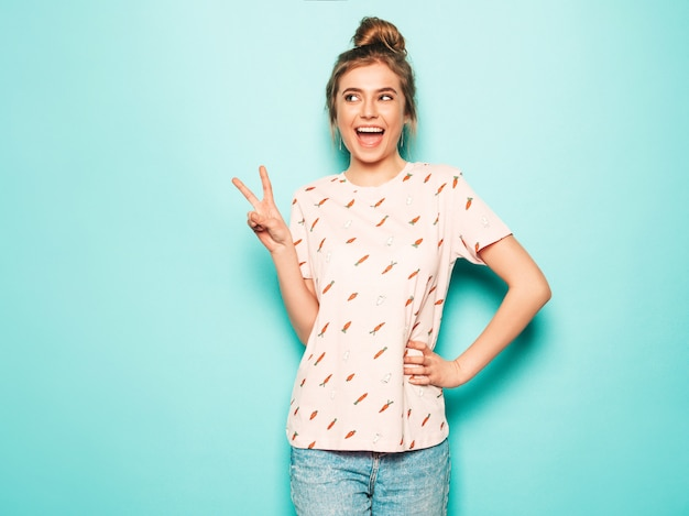 Young beautiful woman looking at camera. trendy girl in casual summer t-shirt clothes showing peace sign. positive female shows facial emotions. funny model isolated on blue