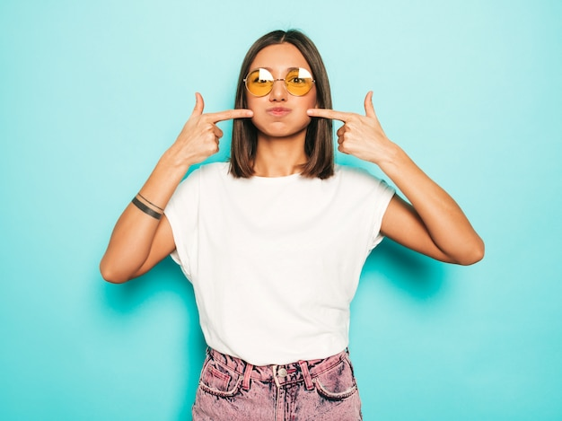 Young beautiful woman looking at camera. trendy girl in casual summer white t-shirt and jeans shorts in round sunglasses. positive female shows facial emotions. funny model blowing her cheeks.