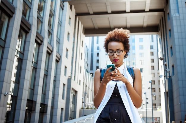 Young beautiful woman looking at phone walking down city