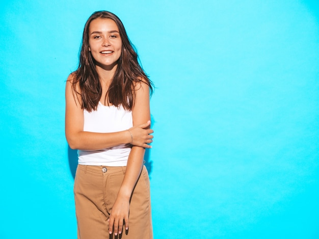Young beautiful woman looking. trendy girl in casual summer clothes. funny and positive female posing near blue wall