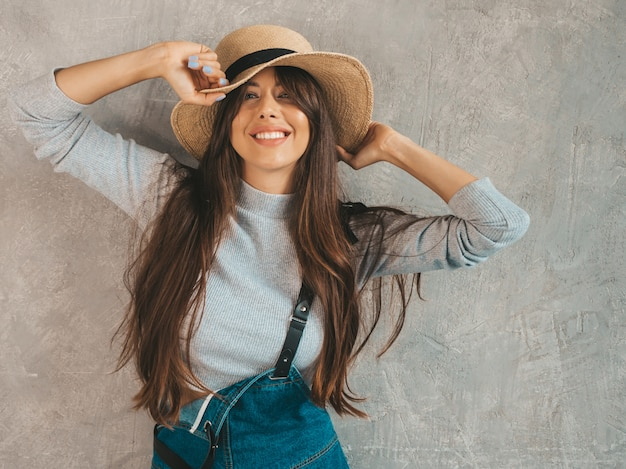 Young beautiful woman looking . trendy girl in casual summer overalls clothes and hat.