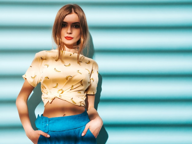 Young beautiful woman looking . trendy girl in casual summer yellow t-shirt clothes. model posing near blue wall