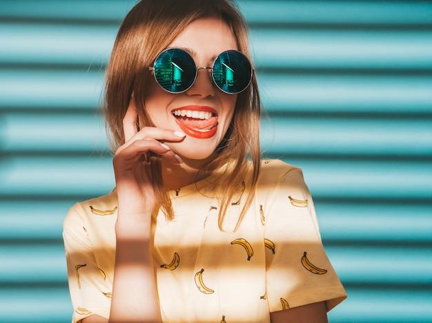 探している若い美しい女性。カジュアルな夏の黄色のtシャツの服でトレンディな女の子。舌を見せて