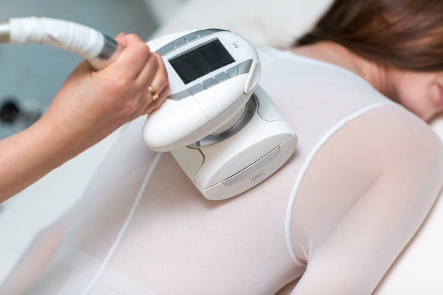Young beautiful woman and lpg massage back procedure in spa clinic. lymphatic drainage massage lpg apparatus process.