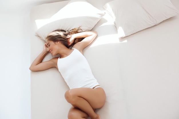 Giovane bella donna sdraiata sul letto nelle prime ore del mattino. sparato dall'alto.